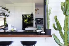 20 a sliding black framed window and a dark stained tabletop with cacti, black metal stools for a chic look