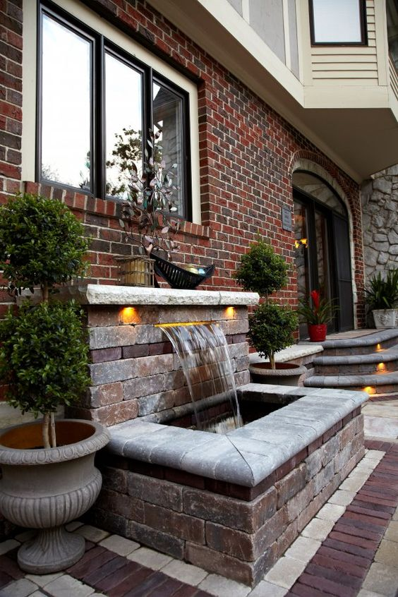 a water feature clad with brick and some additional lights is an elegant and stylish idea for a front yard