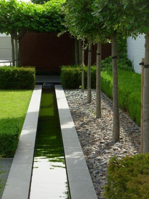 a long minimalist water feature with grey tiles lining it up looks very chic, bold and very simple at the same time