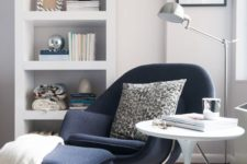 21 a navy chair and a footrest on tall metal legs inspired by mid-century modern designs