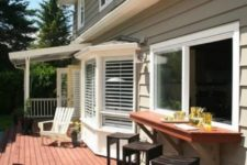 21 a sliding pass through window, a thick stained tabletop and black wooden stools for a deck