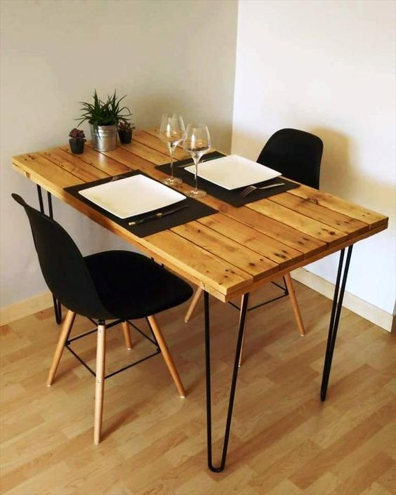 a small and comfy dining table with a pallet tabletop and black hairpin legs looks very chic, black chairs add to it
