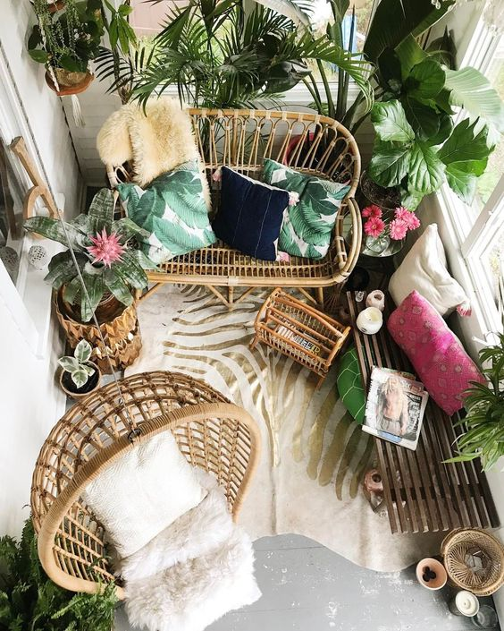 a tropical balcony with rattan furniture, potted torpical plants, colorful pillows and a zebra print rug