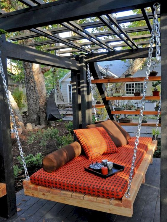 an outdoor pallet daybed hanging on chains is a super cool and relaxing idea for your space