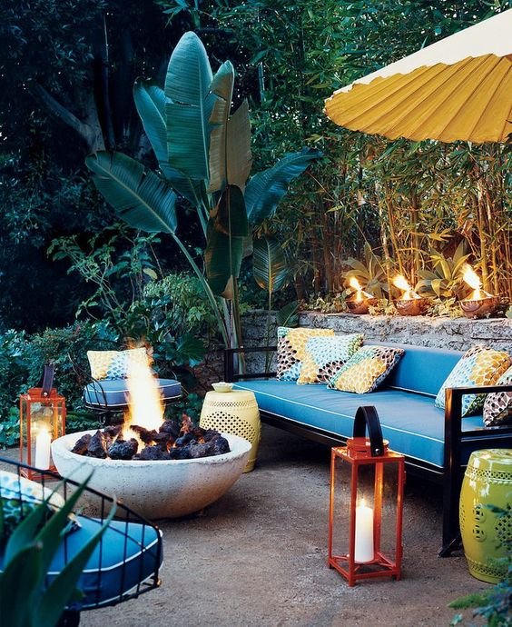 colorful pillows, red lanterns with candles, perforated tables and a large fire bowl to create an ambience
