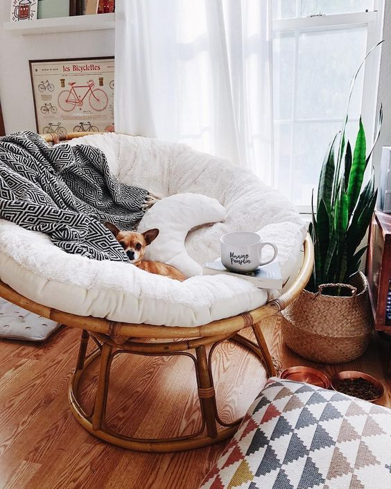 a round rattan chair with cushions and pillows plus a fur throw is extremely cozy to enjoy reading by the window