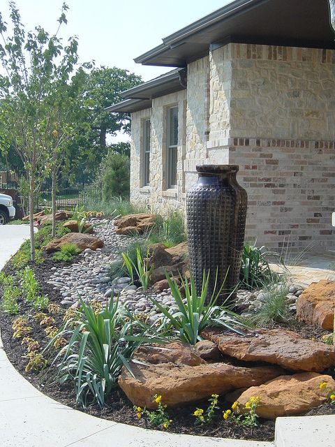 such a no flower front yard with a large vase fountain, rocks, agaves and grasses is a bold modern idea