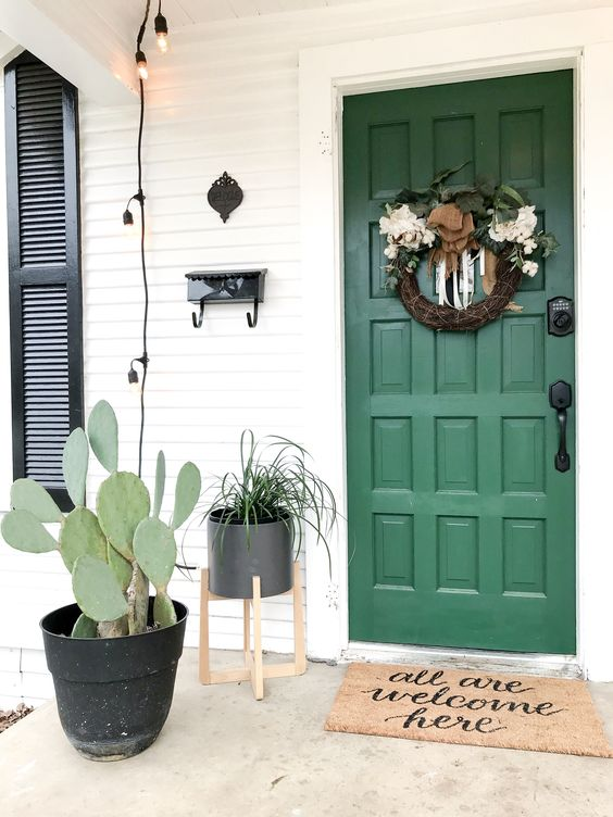 a planter with a cactus and a planter with greenery on a stand match the green door and a wreath adds charm