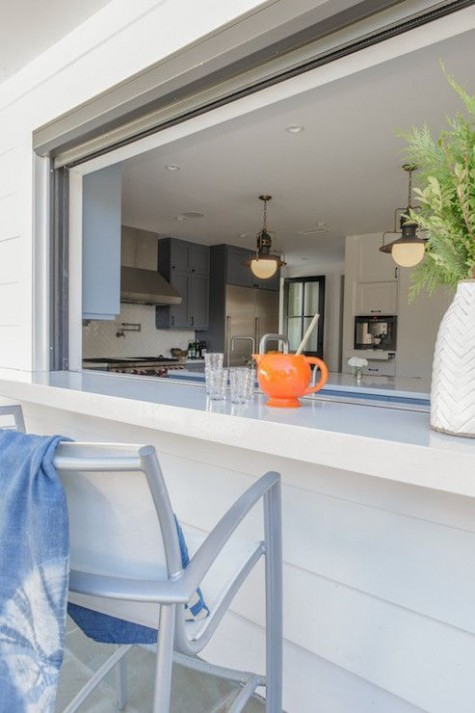 a roll up window with a white countertop and comfy chairs is ideal to have an outdoor meal