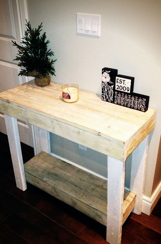 a simple rustic console table built of pallet wood painted white or stained in a light shade
