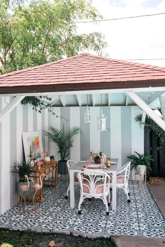 a tropical patio with a dining space done with white and pink rattan chairs, pink flamingos, a rattan bar table and potted plants