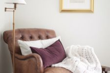 23 a vintage-inspired leather chair in brown with pillows and a knit blanket is always a good diea to try