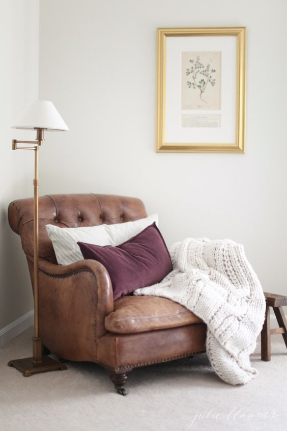 a vintage-inspired leather chair in brown with pillows and a knit blanket is always a good diea to try