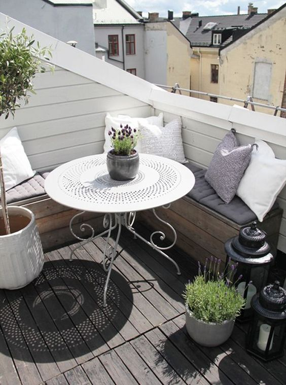 pillows, candle lanterns, potted greenery and blooms make the balcony more inviting and welcoming