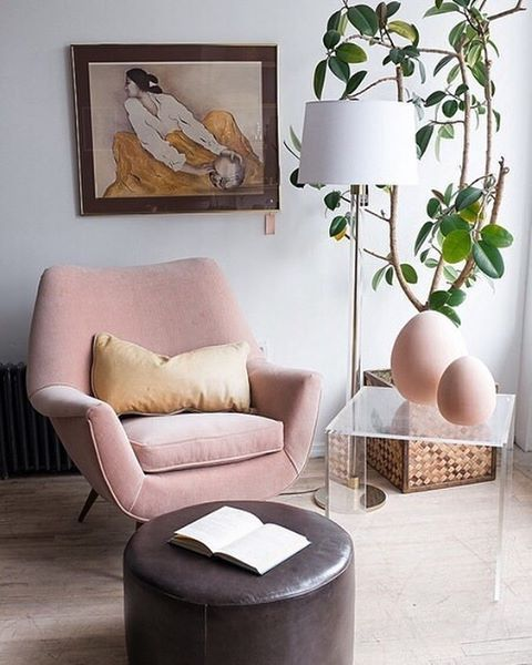 a blush mid-century modern chair with curves and angles is a cool piece, and a brown ottoman contrasts it