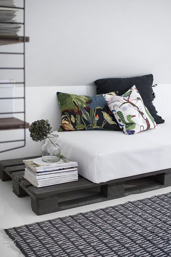 a dark stained pallet daybed with a comfy mattress and printed pillows is a cool idea for a living room