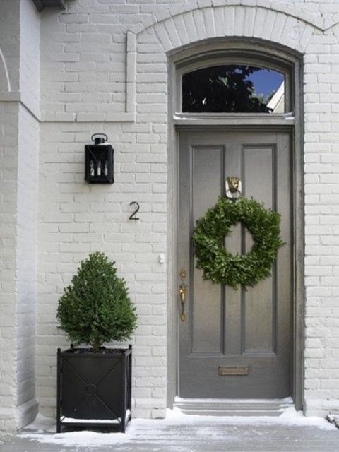 a single black planter with a tree and a matching wreath on the door make up a catchy and welcoming porch