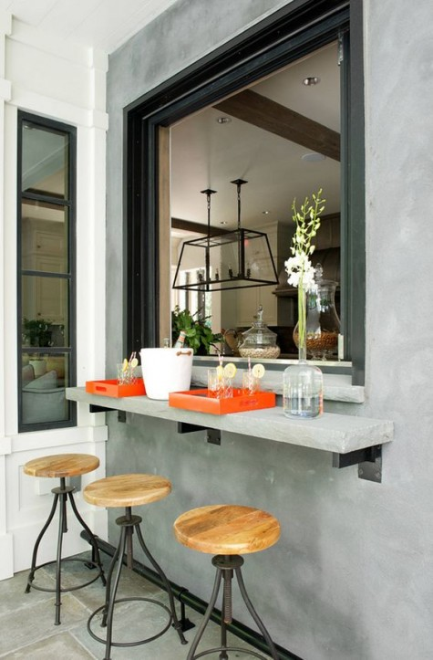 an oversized roll up window and a small concrete tabletop and metal and wood stools for an industrial feel