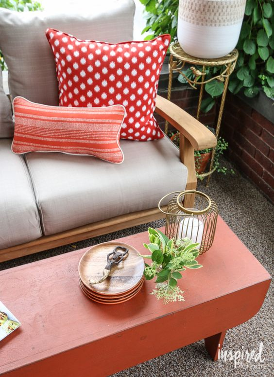 colorful pillows, a candle lantern and potted greenery make up the whole space sprucing it up