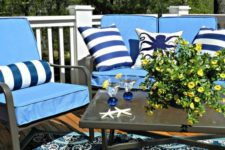 24 colorful pillows in blue and white for a nautical feel and star fish on the table plus a matching rug