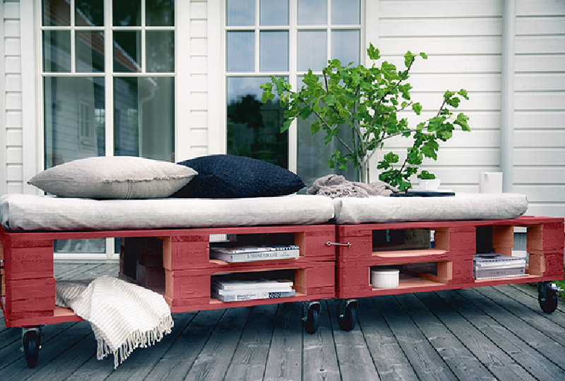a bright red pallet daybed with cutout storage spaces, casters and comfy cushions