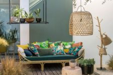 25 a welcoming tropical terrace with a rttan sofa, colorful pillows, a jute rug, wicker baskets and a wicker lampshade plus potted plants