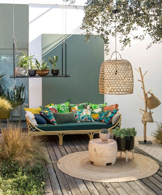 a welcoming tropical terrace with a rttan sofa, colorful pillows, a jute rug, wicker baskets and a wicker lampshade plus potted plants