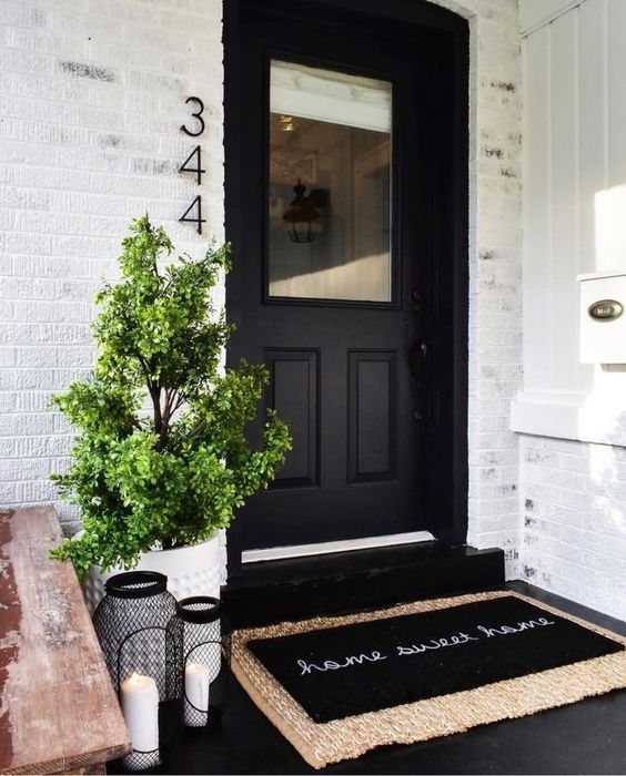 a white planter with a mini tree and black candle lanterns plus a black door for a stylish modern look