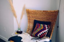 25 a woven chair on a stand with pillows, thrwos and blankets is a stylish idea for a boho space