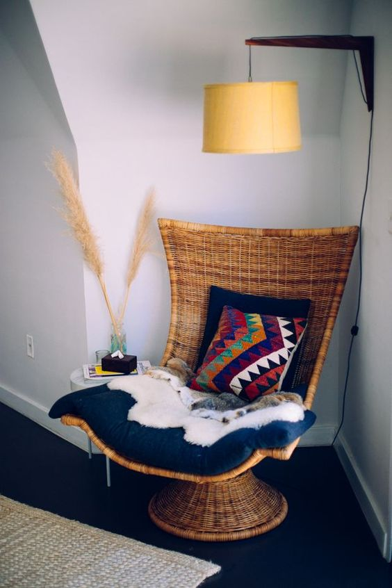 a woven chair on a stand with pillows, thrwos and blankets is a stylish idea for a boho space