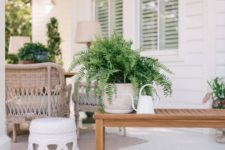 25 potted greenery, a small coffee table and a watering can for decorating a front porch