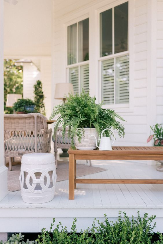 potted greenery, a small coffee table and a watering can for decorating a front porch