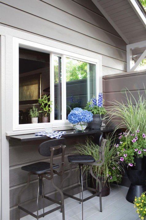 sliding windows and a sleek narrow windowsill as a bar plsu industrial stools in dark metal and potted blooms