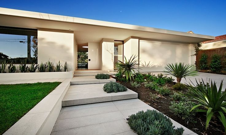 white concrete and stone contrast the greenery and the green lawn that are represented here