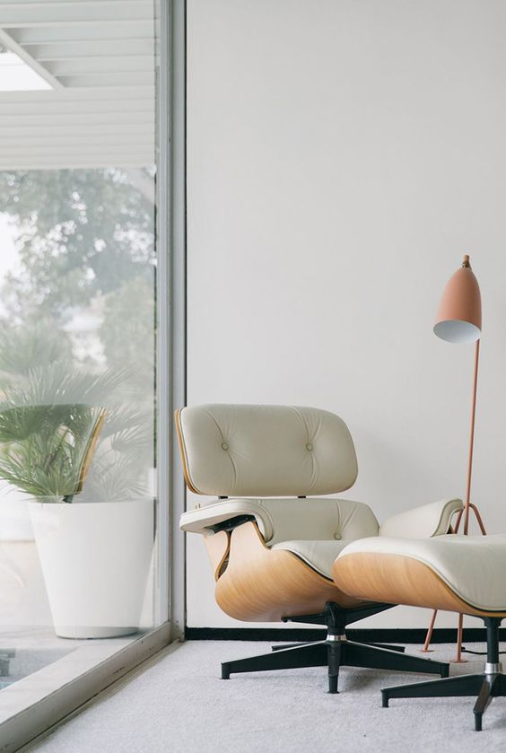 Eames lounge chair of plywood and white leather and a matching footrest by the window