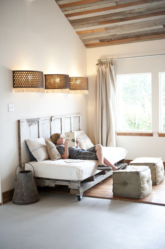 a reading nook fitted with a pallet daybed on casters and a matching headboard brings a shabby chic feel