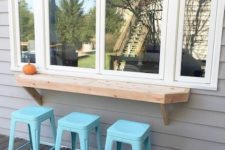 26 a simple window, a thick wooden tabletop and bright blue stools for a simple rustic space
