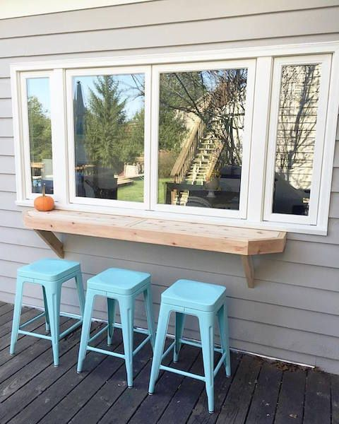 a simple window, a thick wooden tabletop and bright blue stools for a simple rustic space