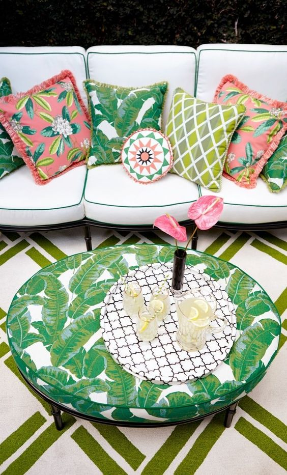 make up a boho patio with a large neutral sofa with colorful pillows and a tropical leaf print table