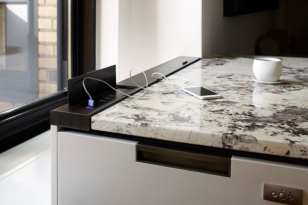 oxidized metal enclosure provides the charging ports in this uber contemporary kitchen without compromising on design