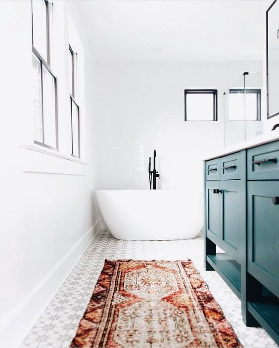 a bright eclectic bathroom done in white and neutrals and accented with a red boho rug and a teal vanity