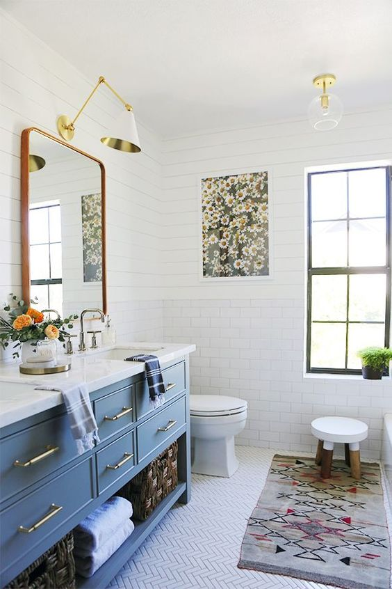 a colorful eclectic bathroom with a blue vanity, a colorful rug and a floral artwork