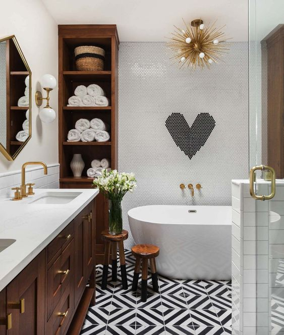 a contemporary meets mid century odern bathroom in black and white with much rich colored wood and gilded touches