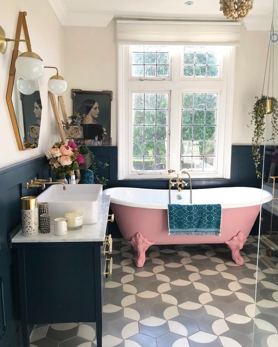 a gorgeous pink roll top clawfoot bathtub and statement tiles on the floor, all pulled together with a navy decor and statement lighting