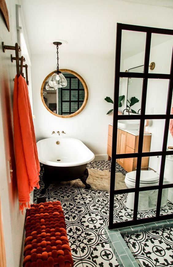 a mid century modern meets contemporary bathroom done in black and white and accented with coral