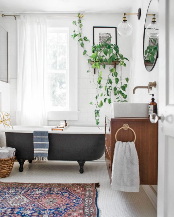 a vintage eclectic bathroom with a boho rug, a vintage black bathtub, potted greenery and a floatign vanity with a sink