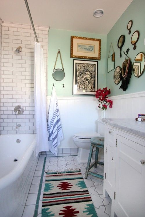 a vintage meets boho chic bathroom, with lots of mirrors and paintings, with a colorful rug and subway tiles