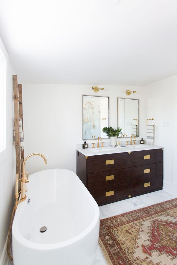 an art deco meets boho eclectic bathroom with lots of brass, boho rugs and a dark stained vanities