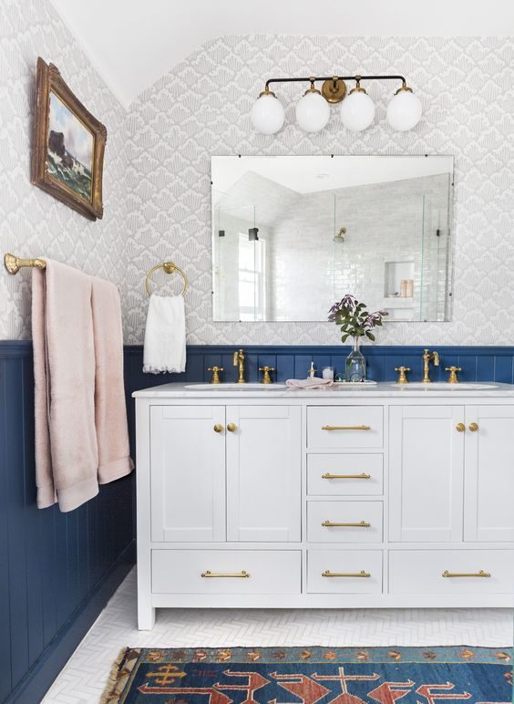 an eclectic bathroom in navy, grey and pink with gilded touches shows off the beauty of vintage and boho styles