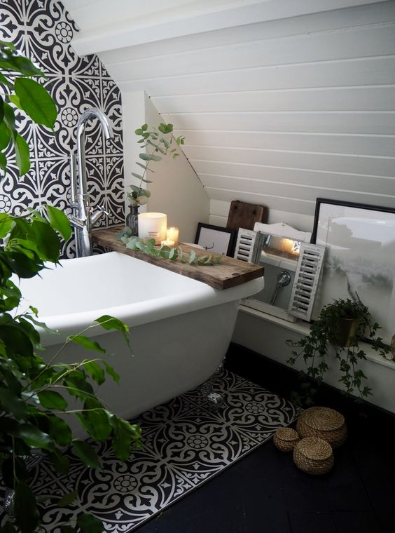 an eclectic bathroom with black and white art deco tiles, with boho touches like wicker containers and potted greenery and decor